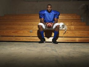 Portrait of an American football player sitting on bench with ba